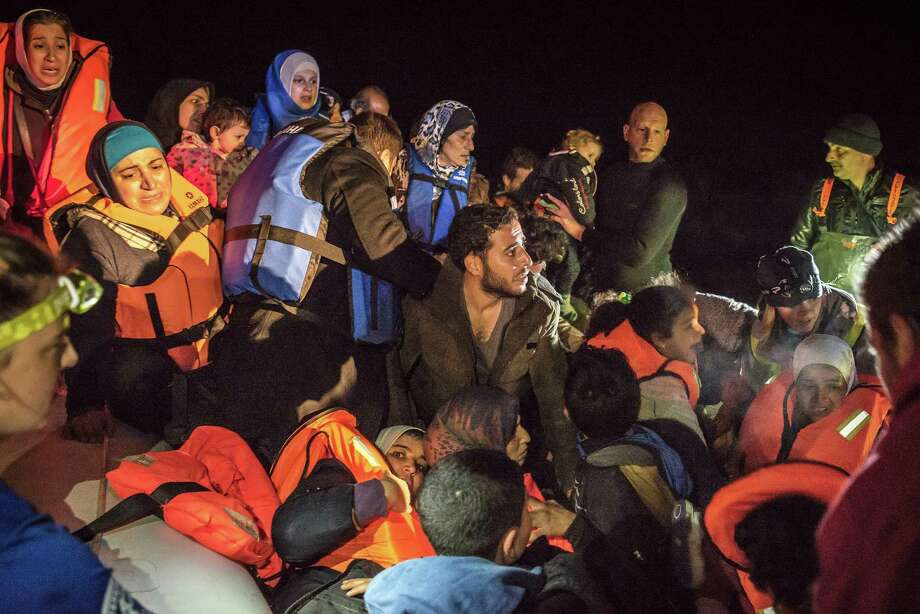 Migrants in an overcrowded raft are helped by rescuers after a sea crossing, on the shore of the island of  Lesbos, Greece, on Sunday.  Photo: SERGEY PONOMAREV, STR / NYTNS