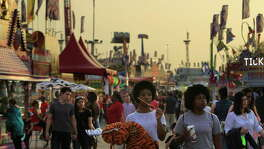 People enjoy the midway and carnival as the sun sets at the Houston Livestock Show and Rodeo, Tuesday, March 15, 2016, in Houston.