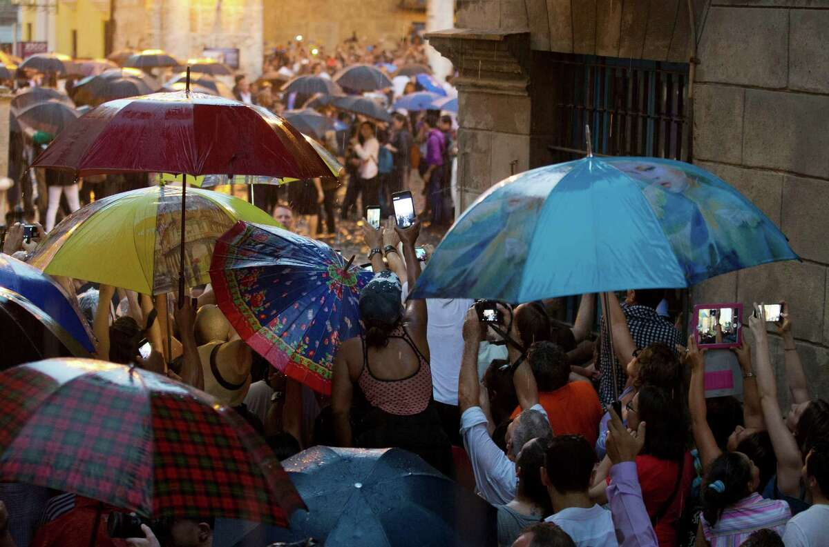 Cubans and tourists strain in the rain to get a glimpse of President Barack Obama as his delegation visits Cathedral Square in Old Havana, Cuba, Sunday, March 20, 2016. Obama's trip is a crowning moment in his and Cuban President Raul Castro's ambitious effort to restore normal relations between their countries.