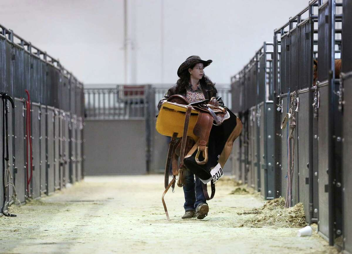 Logan Brown from Tennessee carries her saddle as she packs up on the last day of the Houston Livestock Show and Rodeo on Sunday.