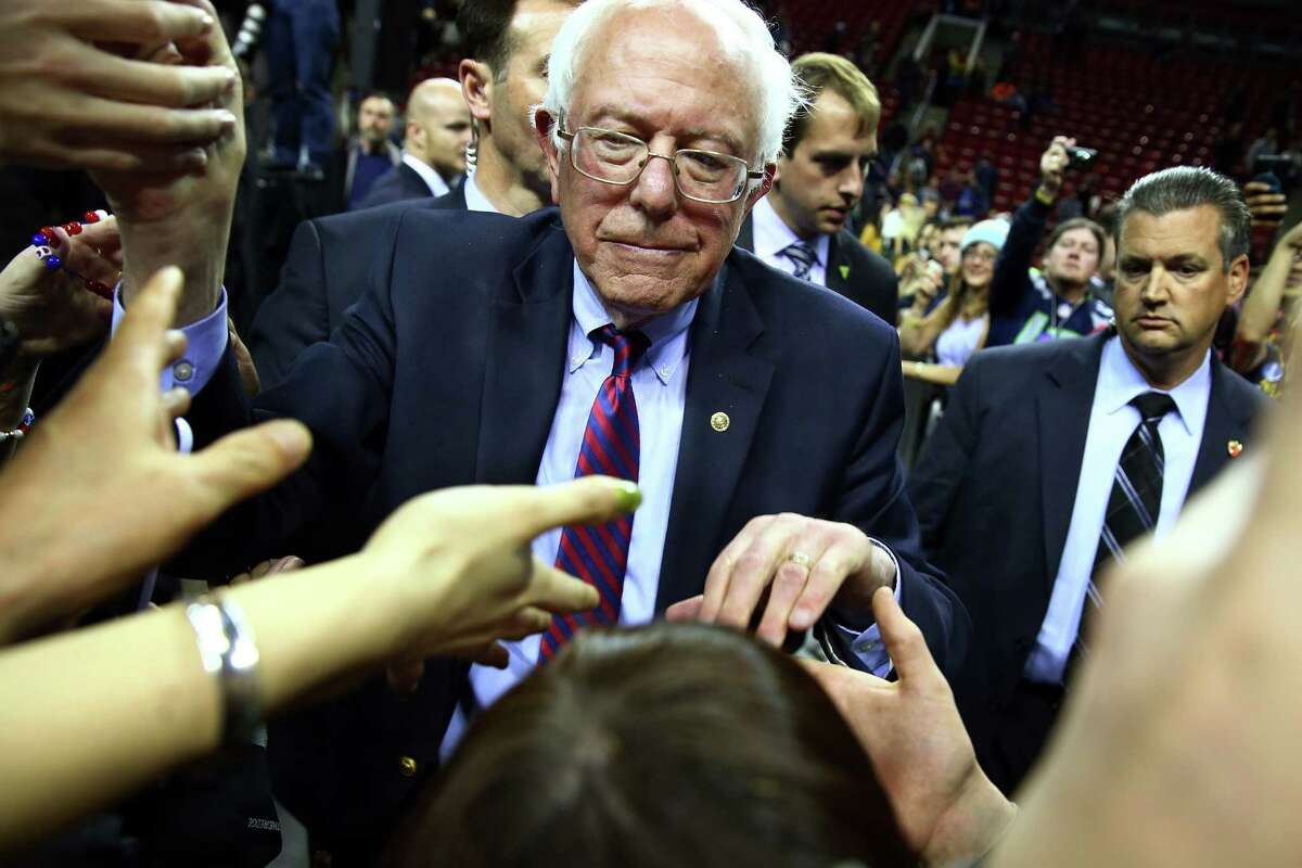 Bernie Sanders shakes hands with supporters at a rally at Key Arena, Sunday, March 20, 2016.