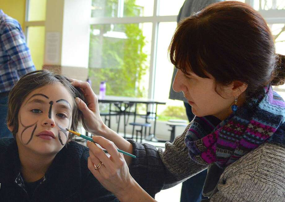 Rachel Rockwell creates a decorative facial Monarch butterfly for Dana Cheng, 7, at the Congregation for Humanistic Judaism celebration of Purim. Photo: Westport News / Jarret Liotta / Westport News