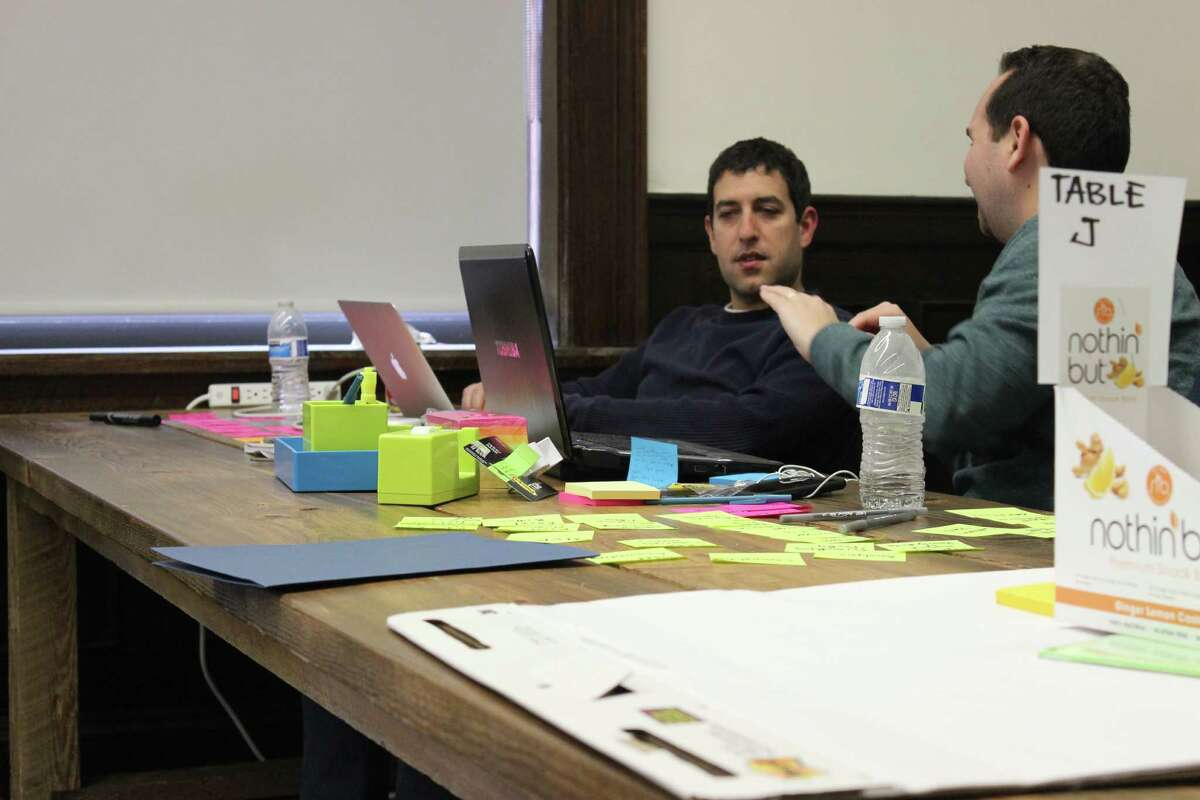 Rick Rosenthal, right, works with Mike Melmed to develop the outline of a business plan for Help Button Excel, with the pair winning the 2016 installment of Startup Weekend Stamford held March 18-20 in Stamford, Conn. Photo by Simon Silverleaf courtesy Startup Weekend Stamford and the Stamford Innovation Center.