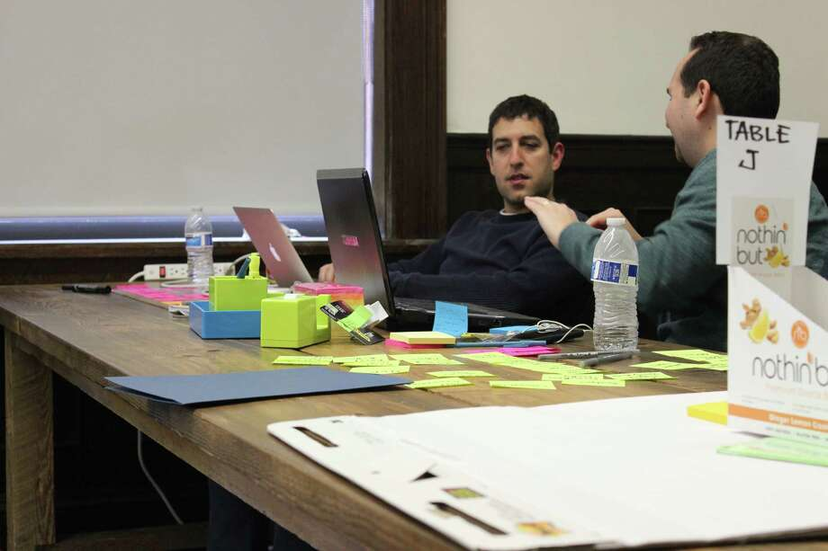 Rick Rosenthal, right, works with Mike Melmed to develop the outline of a business plan for Help Button Excel, with the pair winning the 2016 installment of Startup Weekend Stamford held March 18-20 in Stamford, Conn. Photo by Simon Silverleaf courtesy Startup Weekend Stamford and the Stamford Innovation Center. Photo: Simon Silverleaf /