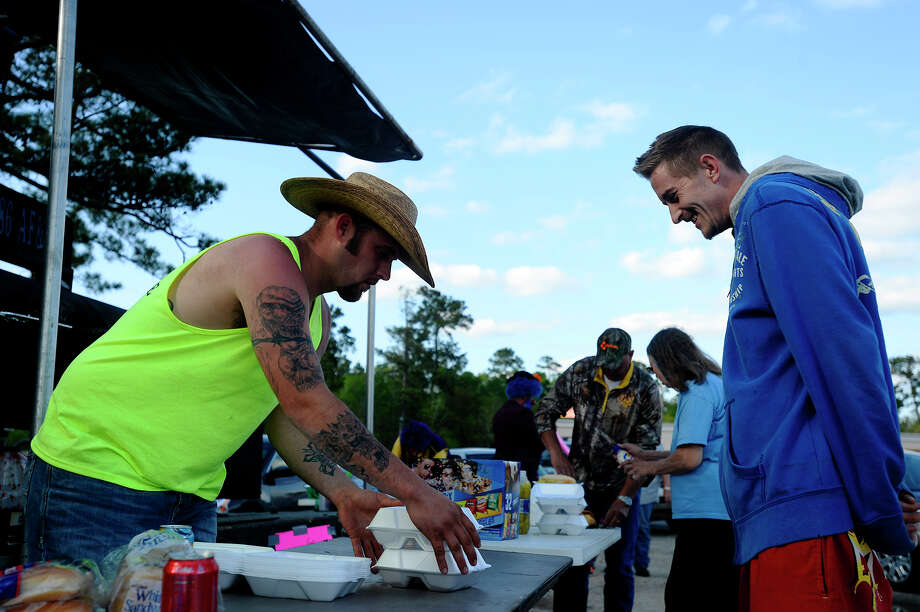 AJ Yellott prepares a plate of food for Jeffery Bean at the corner of Texas 12 and Texas 87 in Deweyville on Saturday afternoon. Bean said he was getting food for his father, whose home was flooded.  Photo taken Saturday 3/19/16 Ryan Pelham/The Enterprise Photo: Ryan Pelham / ©2016 The Beaumont Enterprise/Ryan Pelham