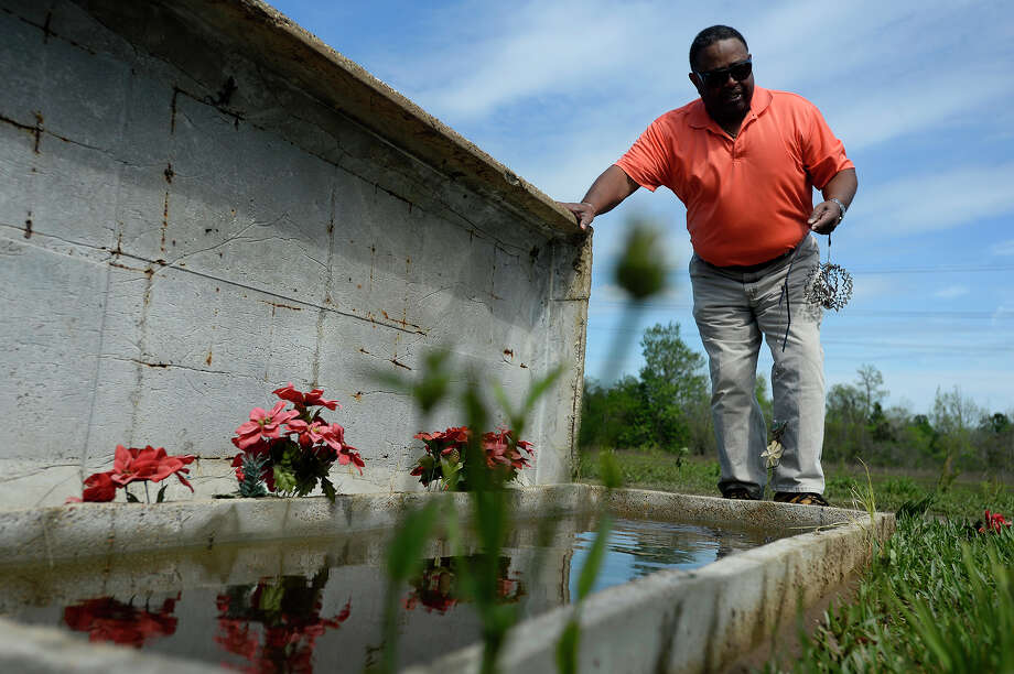 Cecil Williams checks for a casket in the flooded vault of Dewey Mosby in the Hollywood Cemetery in Orange on Saturday. Williams said he was checking on his own family members but also wanted to help locate caskets that had floated away.  Photo taken Saturday 3/19/16 Ryan Pelham/The Enterprise Photo: Ryan Pelham / ©2016 The Beaumont Enterprise/Ryan Pelham
