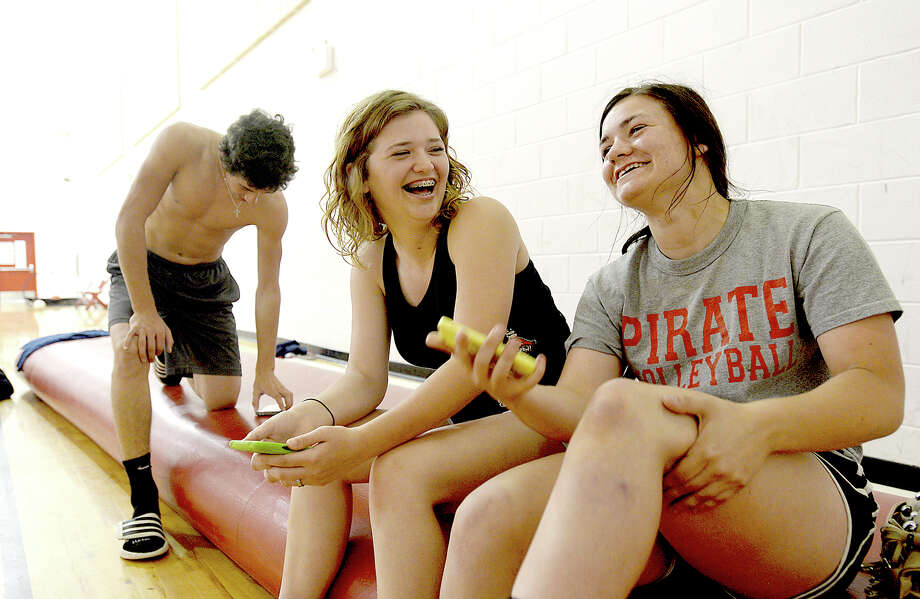 """Regan Williams, 17, (left) jokes with volleyball teammate Gabby Dupuy, 16, while hanging out in the school gym at Deweyville High School Thursday. Regan is among the many students displaced by the floods that devastated the community this week. Gabby, who lives in Mauriceville, was not affected but has been at the school everyday, volunteering to help others as needed. """"I couldn't wait to get out of here [for spring break], but I've been here every day this week,"""" she notes. Photo taken Thursday, March 17, 2016 Kim Brent/The Enterprise Photo: Kim Brent / Beaumont Enterprise"""
