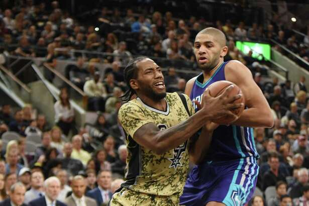 Kawhi Leonard of the San Antonio Spurs drive against Nicolas Batum of the Charlotte Hornets during NBA action in the AT&T Center on Saturday, Nov. 7. 2015.