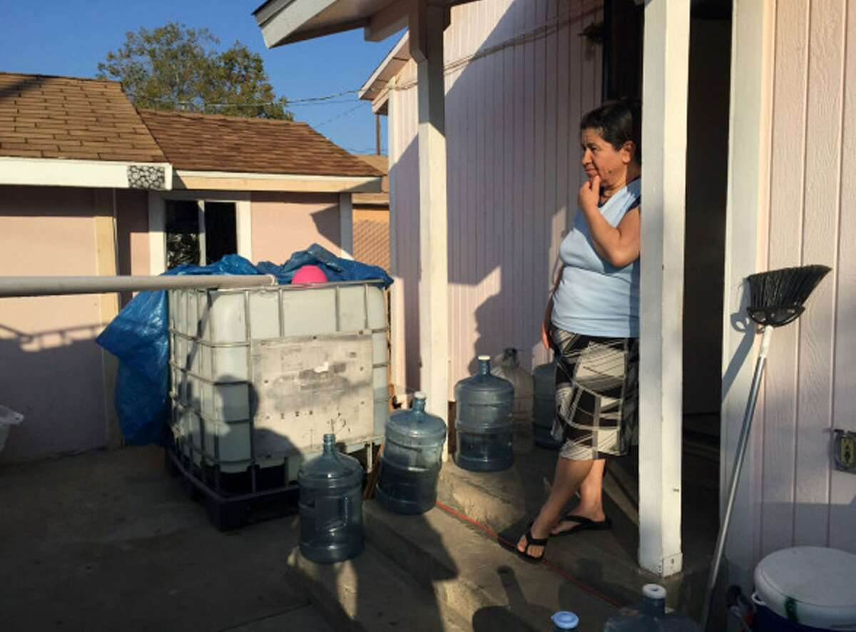 A local nonprofit donated and installed a 265-gallon tank at Socorro Ambriz's house in East Porterville. Every week, Ambriz's brother fills three 55-gallon barrels at a nearby water station. He makes two trips so her family of four can shower, flush their toilets and wash dishes. (Joanna Lin/Reveal)