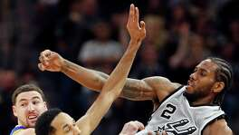 San Antonio Spurs' Kawhi Leonard watches his pass over Golden State Warriors' Klay Thompson (left) and Shaun Livingston during second half action Saturday March 19, 2016 at the AT&T Center. The Spurs won 87-79.