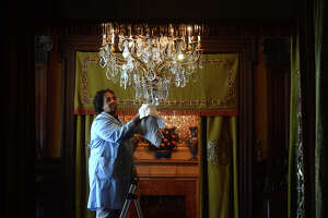 Mary Acclis  cleans a chandelier in the entryway of McFaddin-Ward House while she and Shirley Johnson go about their usual Monday cleaning of the first floor. The women have been working at the museum for 10 and 30 years, respectively. Five days a week, they meticulously clean, polish, vacuum and dust the house and its decorative furnishings. The women have been specially trained in conservation cleaning methods, donning gloves, work coats and shoe coverings, to help protect the house and its contents. Photo taken Monday, March 14, 2016 Kim Brent/The Enterprise