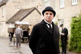 Jim Carter, who plays Mr. Carson, the butler, casts a stern eye over the buildings of Downton village   actually the village of Bampton in Oxfordshire.