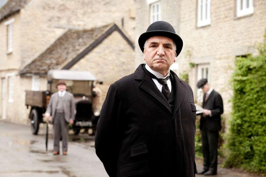 Jim Carter, who plays Mr. Carson, the butler, casts a stern eye over the buildings of Downton village   actually the village of Bampton in Oxfordshire. Photo: Joss Barratt, Carnival Films
