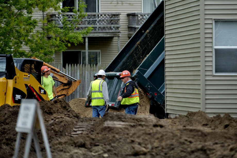 NICK KING | nking@mdn.netA crew works to spread new soil on the lot of a home on George Street recently in Midland. Photo: Nick King/Midland  Daily News