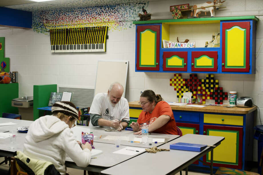 NEIL BLAKE | nblake@mdn.netClay Instructor George Patton assists Laura Lamberto of Midland. Lamberto decided to design a bird house. The class is one of the Express Yourself Artshop courses and lasts eight sessions covering basic handbuilding techniques. Photo: Neil Blake/Midland  Daily News