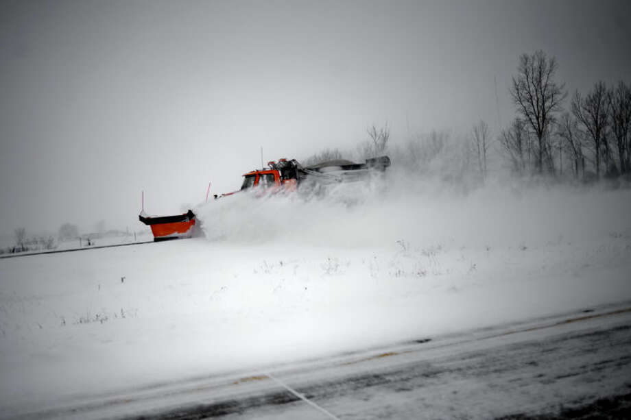 NICK KING | nking@mdn.netA truck with a snowplow clears a road after the snowstorm last week. Photo: Nick King/Midland  Daily News