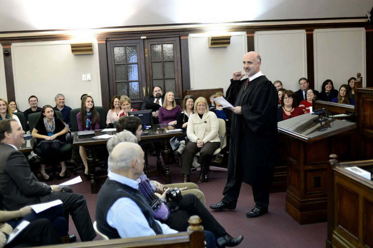 NICK KING | nking@mdn.net75th District Court Judge Michael Carpenter, right, talks to guests during his investiture ceremony Monday in the Historic Courtroom at the Midland County Courthouse.