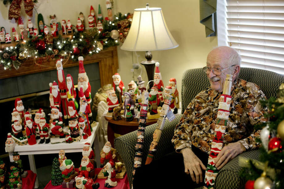 NICK KING | nking@mdn.netSurrounded by a selection of his carved figures, Hugh Clark, 79, formerly of Harbor Beach, smiles as he talks about his life as a carver recently at the Sterling House. Clark has carved thousands of wooden Santas and other figures for family, friends and students. Photo: Nick King/Midland  Daily News