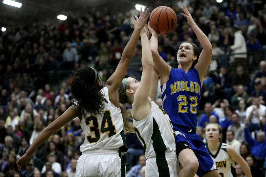 SEAN PROCTOR   sproctor@mdn.netMidland's Jess Walter goes up for a basket against Dow's Carlee McGee and Kaylee Wasco Tuesday during their game at Dow High School. The Chemics defeated the Chargers 48-39. Photo: Sean Proctor/Midland  Daily News