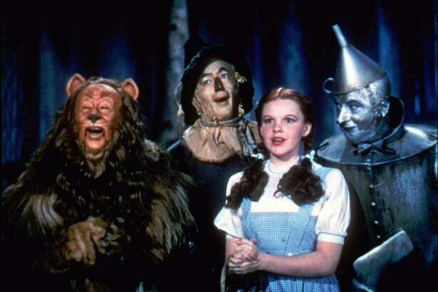 """The Cowardly Lion (Bert Lahr), The Scarecrow (Roy Bolger), Dorothy (Judy Garland), and The Tin Man (Jack Haley) traverse a danger-filled Yellow Brick Road in """"The Wizard of Oz"""" (1939).   Photo: Courtesy of Warner Home Video"""