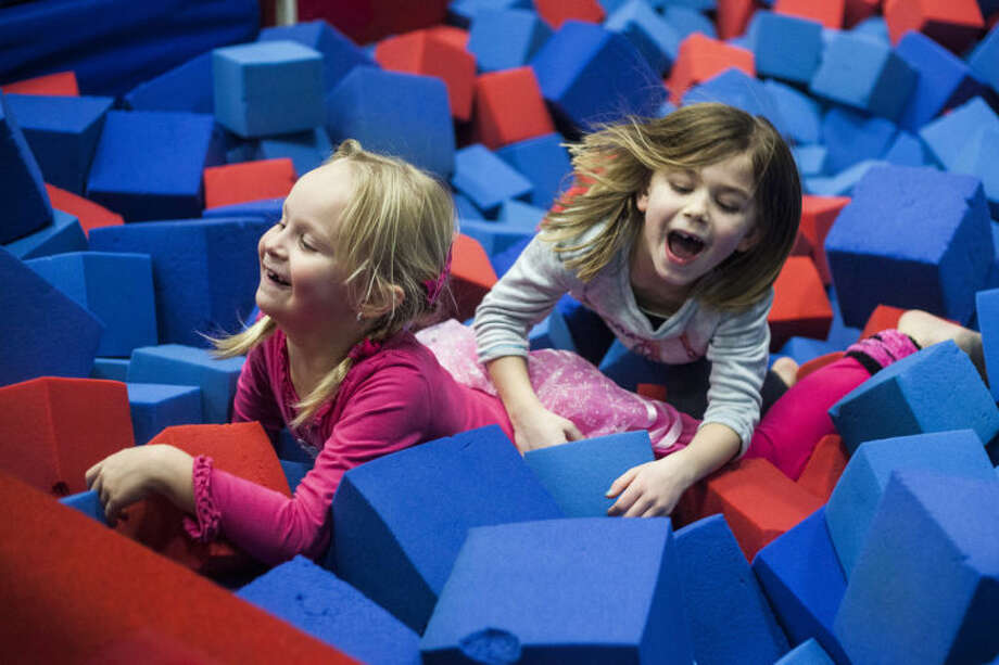 ZACK WITTMAN | for the Daily NewsElizabeth Garner, left, laughs in the foam pit with her friend Ella Wolikski, 7, during Garner's seventh birthday party at the Mid Michigan Gymnastics Center in Freeland.
