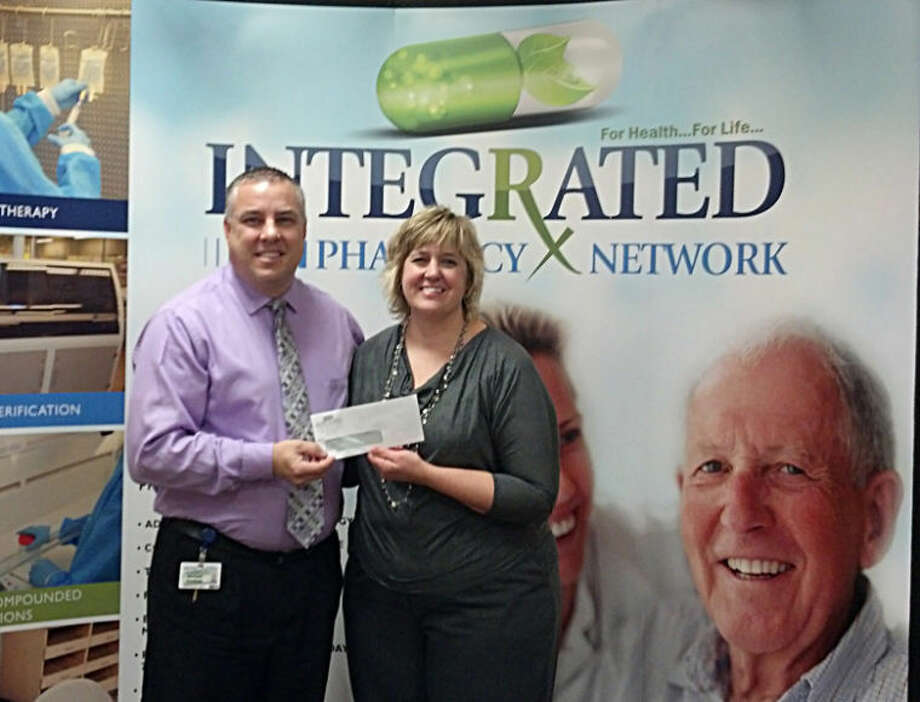Photo providedMichael Gardner, CEO at Integrated Pharmacy, gives the donation to Robin Greiner, shelter coordinator.