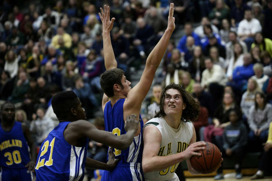 SEAN PROCTOR | sproctor@mdn.netDow's Evan Marquardt looks to the basket against Midland's Austen Irrer, center, and Virgil Walker Tuesday during their game at Dow High School. The Chargers defeated the Chemics 49-44. Photo: Sean Proctor/Midland  Daily News