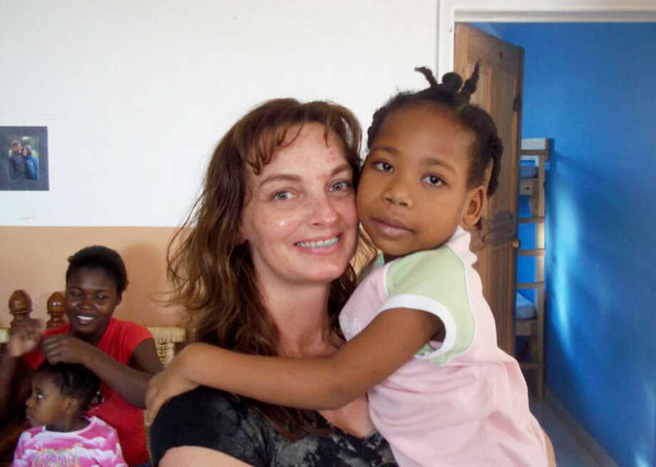 Photo providedLonna Allen of Coleman holds her foster daughter, Elizabeth. Lonna and her husband, Jay, met Elizabeth during mission trips to Haiti after the 2010 earthquake. Elizabeth, known as Eli, is living with the Allens in Coleman awaiting word if she will be allowed to be formally adopted.