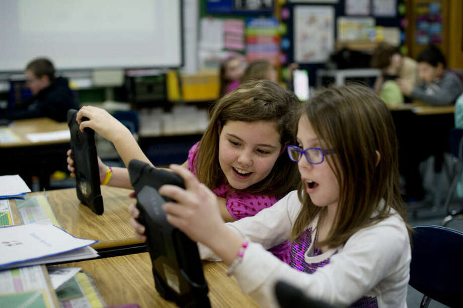 NEIL BLAKE | nblake@mdn.netEmma Dingman, left, and Jadyn King play math based games at Carpenter Street School in Tom Venman's fourth grade class. The games are a fun way to practice multiplication tables and other foundational math skills. Photo: Neil Blake/Midland  Daily News
