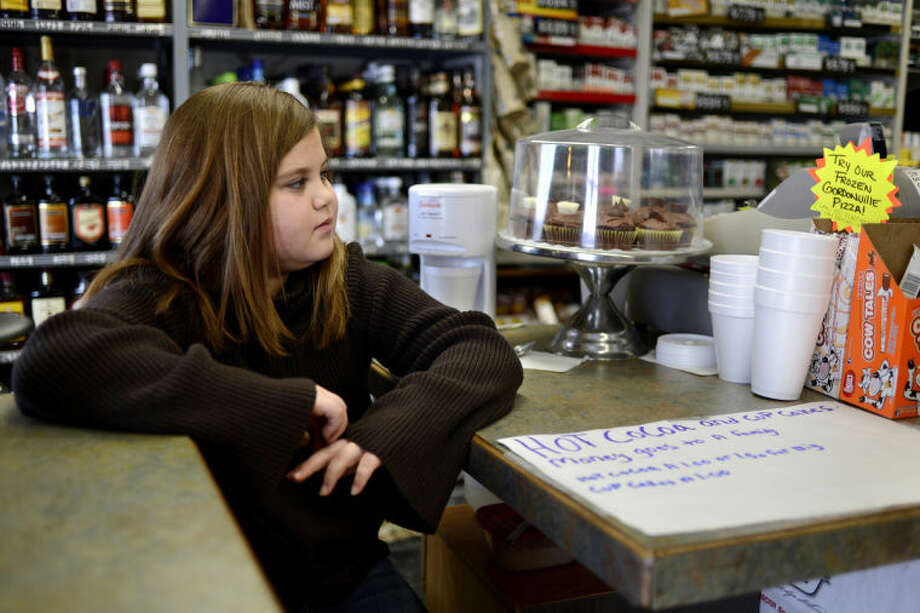 NICK KING | nking@mdn.netHaley Hunter, 11, waits for customers while selling hot chocolate and cupcakes at the Gordonville Grocery off Meridian Road. Haley has been making and selling baked goods at her family's store to help out people in need. Photo: Nick King/Midland  Daily News