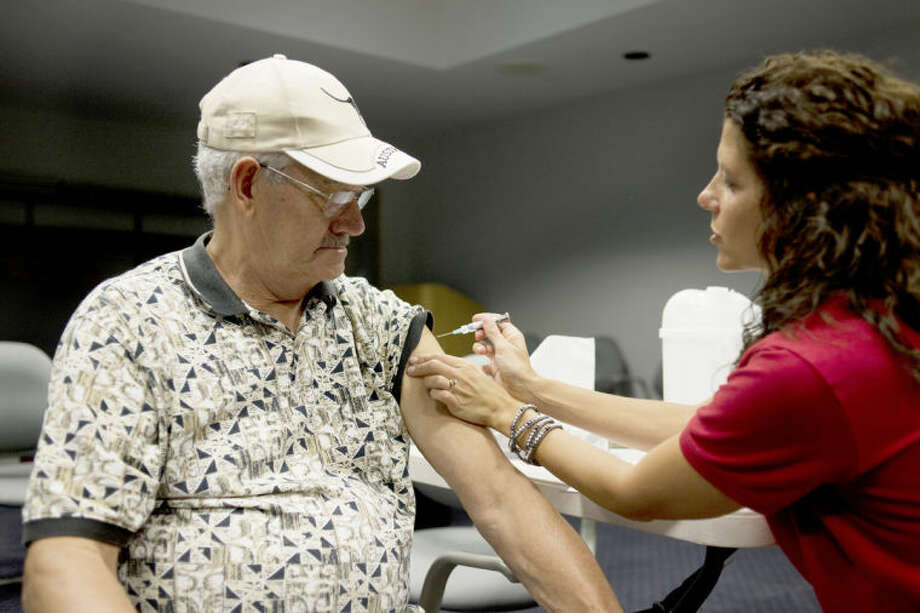 NEIL BLAKE | nblake@mdn.netJim Chambers of Sanford gets a flu shot from Travel Immunization Nurse Nicole Swanton at the Midland County Services Building. Cases of the flu are on the increase in the region, local health officials said. Photo: Neil Blake/Midland  Daily News