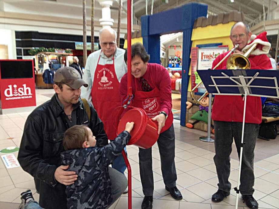 Photo providedAKtion Club member Jim Pankey, club adviser Alex Rapanos and Kiwassee Kiwanis Club member Bill Burk help a boy place his donation in the Salvation Army kettle at the Midland Mall.
