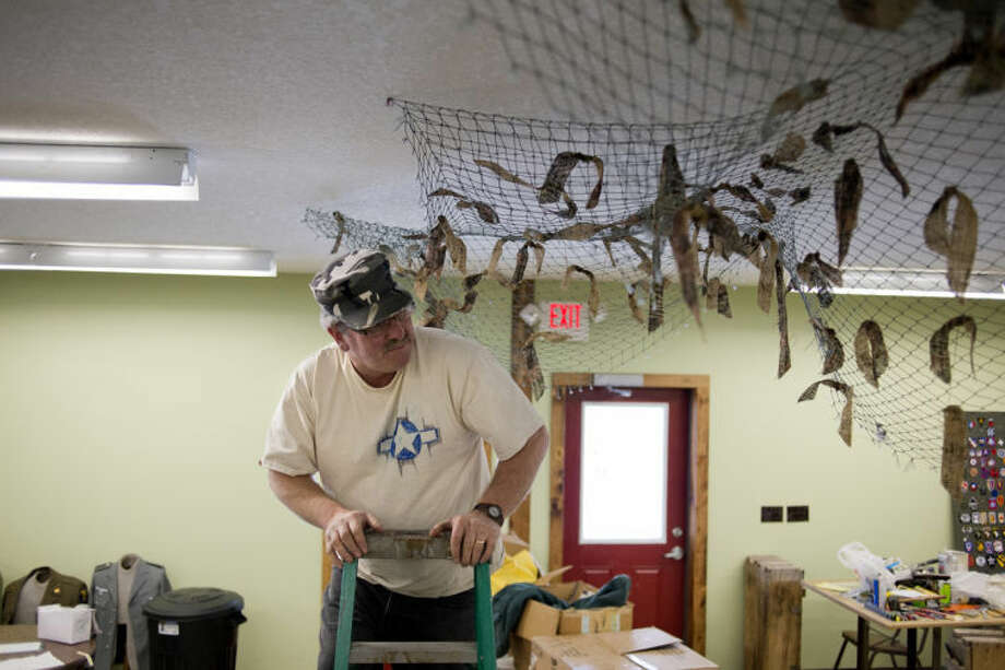 NEIL BLAKE | nblake@mdn.netLarry Stebbins climbs down a ladder after hanging up netting over the cash register area at Headquarters Co.'s new location. Photo: Neil Blake/Midland  Daily News