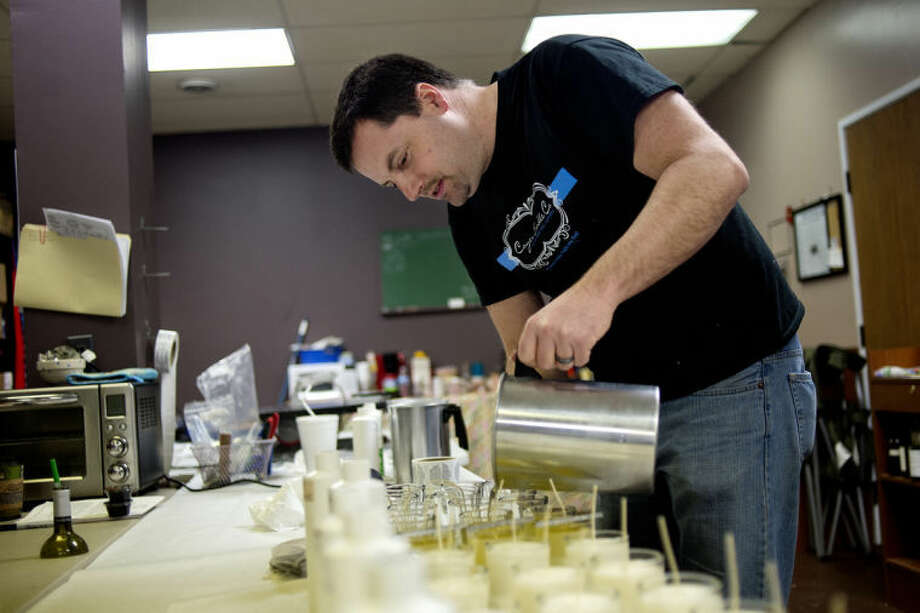 NICK KING | nking@mdn.netScott Coyer pours hot wax into candle containers at the Coyer Candle Co. Thursday in Midland. Photo: Nick King/Midland  Daily News