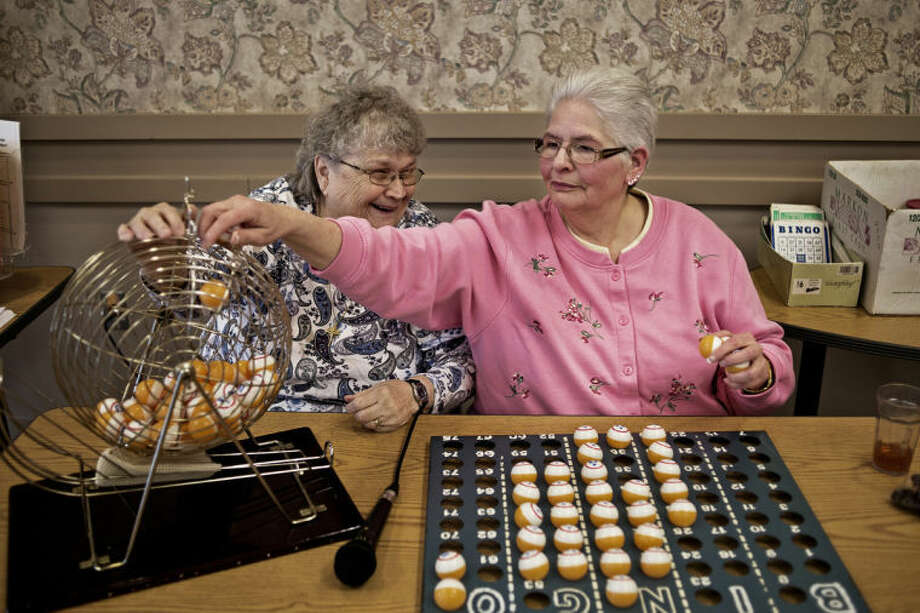 SEAN PROCTOR | sproctor@mdn.netPat Gamer, left, and Pam Celley, both of Sanford, laugh while putting away the Bingo balls Wednesday at the Trailside Senior Center in Midland. Places like the Trailside Senior Center are great for seniors looking to connect with others, which will make them less likely to fall victim to abuse. Photo: Sean Proctor/Midland  Daily News