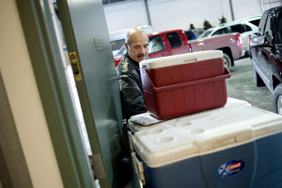 NICK KING | nking@mdn.netVolunteer Phil Sanchez carts coolers of food to his car at the Trailside Senior Center before delivering Meals on Wheels to area seniors. Photo: Nick King/Midland  Daily News