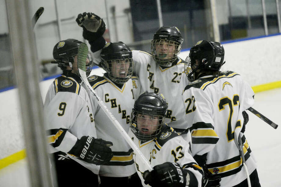 NICK KING | nking@mdn.netFrom left, Dow's Davis Millholland, Travis McNally, Zachary Paisley, Michael Leslie and Cayetano Wagner celebrate McNally's goal against Midland during the second period Monday at the Saginaw Bay Ice Arena. Dow won 7-2.