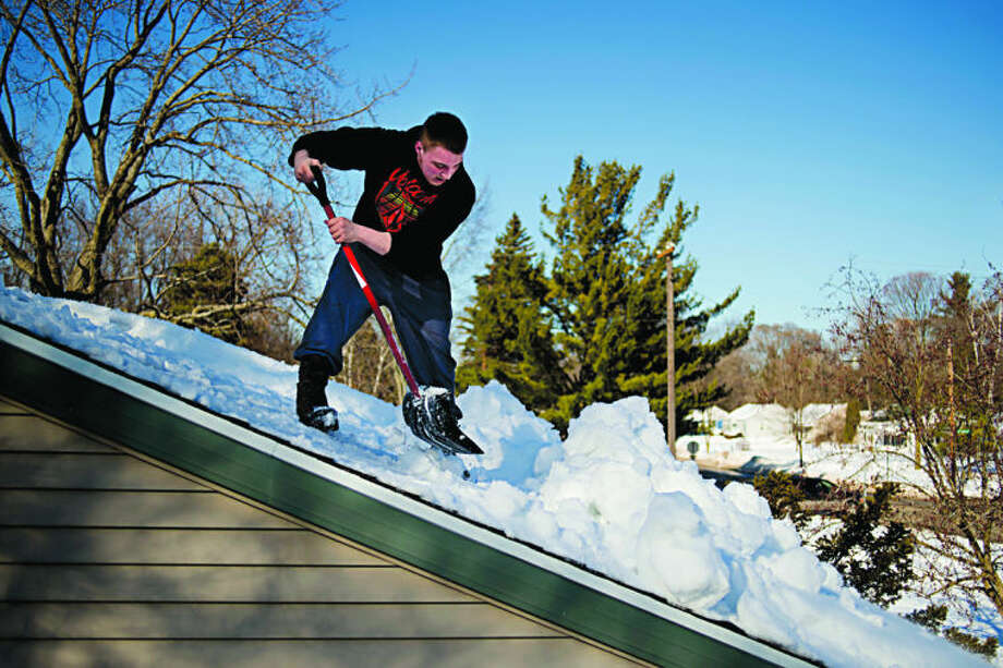 "NEIL BLAKE | nblake@mdn.netJoel Finney, 19, shovels snow from his grandmother's roof in Midland on Wednesday. ""It's a lot heavier than I thought it would be,"" Finney said. As the temperatures rose, the water saturated snow put additional stress on roofs already piled high with snow. Photo: Neil Blake/Midland  Daily News"