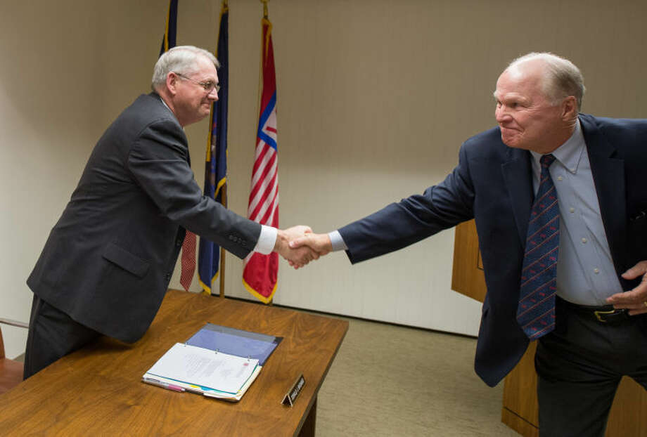 Retiring SVSU President Eric Gilbertson, right,congratulates Donald Bachand after the Midland resident was appointed the institution's new president at Monday's Board of Control Meeting. Bachand's first day as president will beMonday, Feb. 17. (Photo provided by SVSU's Michael Randolph)