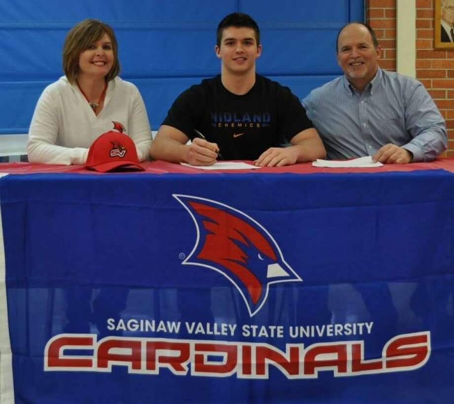 Midland High's Michael Alexander, center, signs his letter of intent with Saginaw Valley State University football on Wednesday.