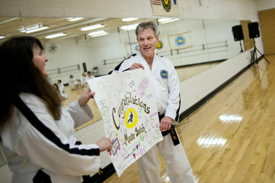 Midland Community Center Taekwon-Do instructor and Midland resident Terry Batch, right, and student and instructor Susan Kirk show off a poster signed by class members congratulating Batch on earning his eighth-degree black belt. Batch was surprised with the poster and a cake at the end of his Thursday class. Photo: Nick King/Midland  Daily News