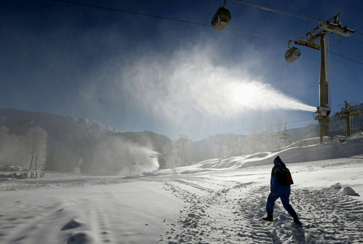 AP Photo   Luca BrunoA volunteer walks toward a snow cannon near Extreme Park, which is the venue for the freestyle skiing and snowboarding disciplines at the Sochi 2014 Winter Olympics.