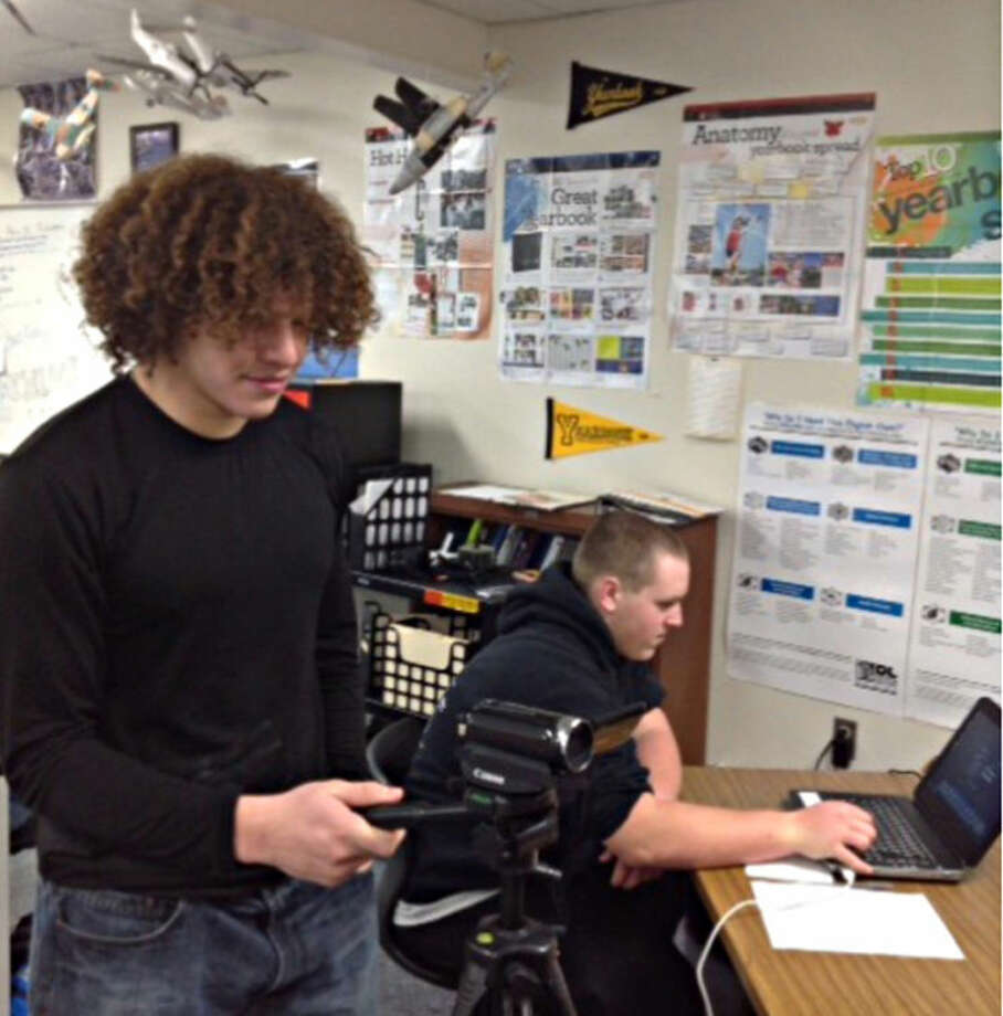 Photo providedSeniors Alberto Flores (front) and Cody Russell test equipment before broadcasting a game at Hemlock High School.  Photo: Jack Telfer