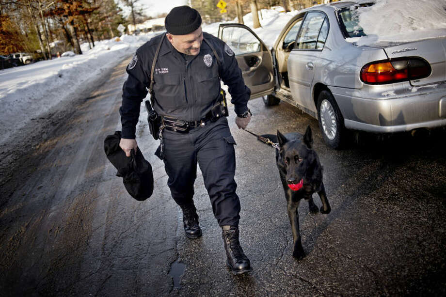 "SEAN PROCTOR | sproctor@mdn.netMidland City Police Officer John DuBois walks back to his vehicle with his dog Tza'Yid after setting up a ""K-9 sniff test"" on Thursday afternoon. Tza'Yid is a narcotics and human odor tracking dog, and it is important to continually train the dog so he is always prepared when called upon. Photo: Sean Proctor/Midland  Daily News"
