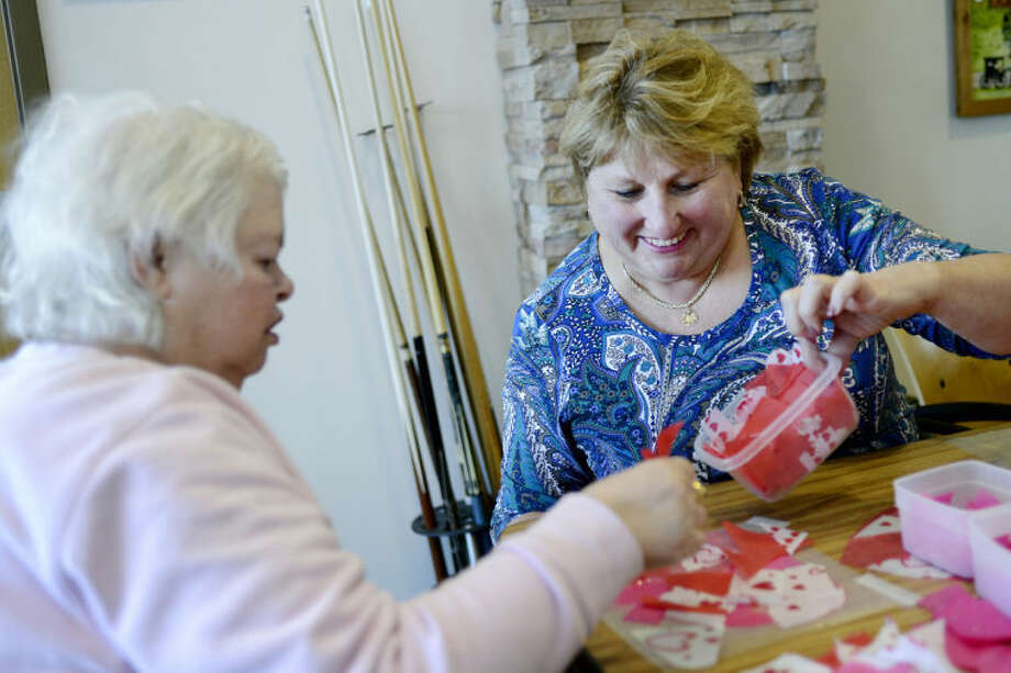 NICK KING | nking@mdn.netVolunteer Linda Horbal, right, helps resident Marcy Pelletier work on Valentine's Day-themed window ornaments Monday at Pinecrest Farms. Photo: Nick King/Midland  Daily News