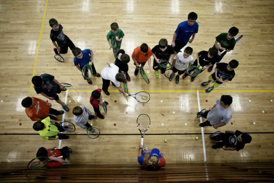 SEAN PROCTOR | sproctor@mdn.net Allie Will helps a group of 6th graders from Jefferson Middle School how to bounce tennis balls on their rackets Thursday afternoon at Jefferson Middle School. Will and her doubles partner, Jan Abaza, also answered question from the group. They both said they enjoyed the chance to get out into the community and teach the kids about their lifestyle and passion. Photo: Sean Proctor/Midland  Daily News