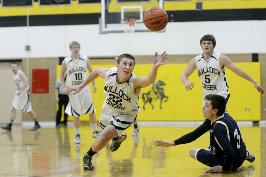 Bullock Creek's Jacob Dean, left, dives for the ball while stealing from Shepherd's Lucas Doyle, right, during the first quarter Tuesday at Bullock Creek High School. Dean teammates Alex Fleming, left, and Drew Roth look on from the background. Shepherd won 54-45. Photo: Nick King   Midland Daily News