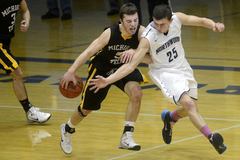 NICK KING | nking@mdn.netNorthwood's Dylan Langkabel, right, attempts to steal the ball from Michigan Tech's Ben Stelzer during the first half Thursday at Northwood University. Michigan Tech won 73-44. Photo: Nick King/Midland  Daily News