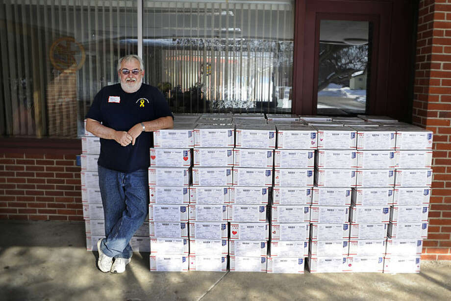 "ZACK WITTMAN | For the Daily News Kevin Ullom, of Midland, leans on care packages from the ""Operation Love from Home"" event on Saturday afternoon at St. John's Lutheran Church. Over 200 volunteers helped create care packages for Midland soldiers through ""Aaron's Gifts From Home"", a program started after Kevin and Debi Ullom's son, Aaron, was killed in July of 2011 in Afghanistan."