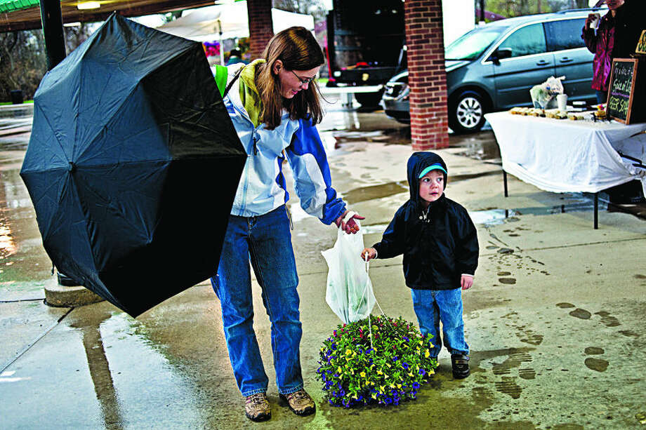 SEAN PROCTOR   sproctor@mdn.net Jennifer Chubb, of Midland, and her son Ajay, 2, walk through the Midland Area Farmer's Market on Wednesday afternoon after buying a Million Bells plant from Bruce Jorck, of Michelle's Flowers, for Mother's Day. The Farmer's Market officially opened last Saturday, and will be open through the summer every Wednesday and Saturday from 6 a.m. to noon. Photo: Sean Proctor/Midland Daily News